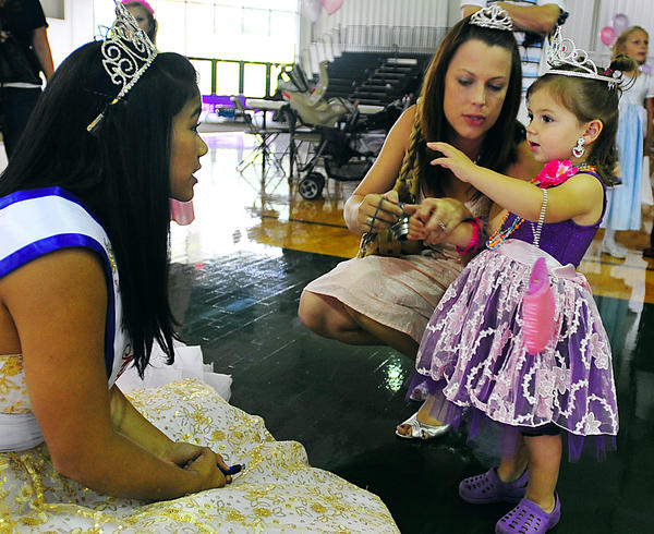 Presley Hays, 2, of Williamsport admires the tiara of Miss Virginia American Junior Teen, Gabby Fernando, Saturday during a party for young princesses at Hagerstown Community College. Mom Samantha Hays stays close.