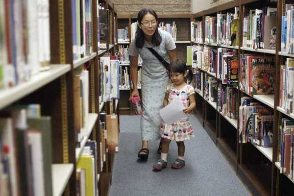 Katsuko Machida, left, and her daughter, Risa, 4, look for another clue during a scavenger hunt that celebrated Los Angeles County Library's 100th anniversary celebration at La Canada Flintridge Library.