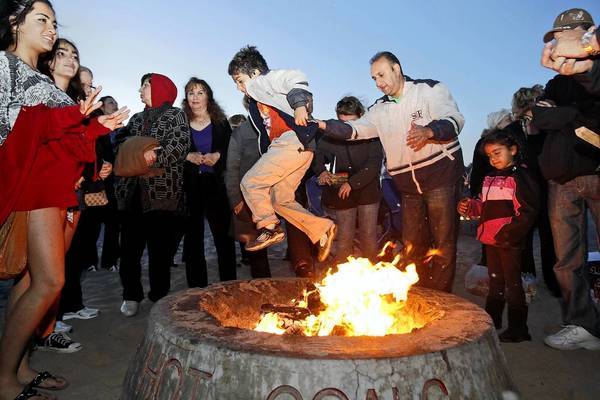 Kianoush Hamadani, center right, of Irvine, helps his son Cameron, over a bonfire in celebration of the Persian New Year in March.