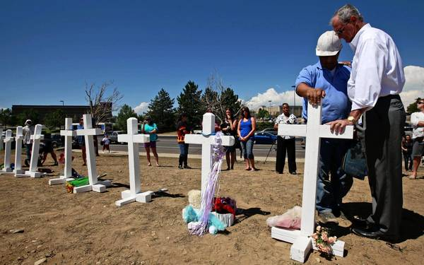 Aurora, Colo., Mayor Steve Hogan, right, prays with Greg Zanis, who erected crosses at a memorial for victims of the mass shooting at the theater across the street.