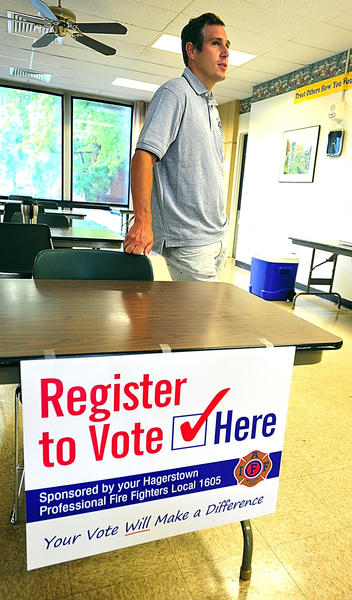 Hagerstown firefighter Geoff Placek waits Saturday morning for a Potomac Towers resident to assist with voter registration.