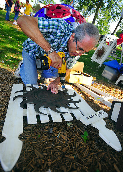 Tom Wilson assembles a decorative fence Saturday during Boonesborough Days. He makes country-style furnishings and decorations.