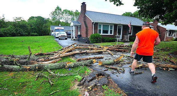 Darryl Sensenbaugh steps over the litter made by a tree that blew across his South Edgewood Drive driveway Saturday. A violent storm brought wind and rain to the Hagerstown vicinity Saturday afternoon.