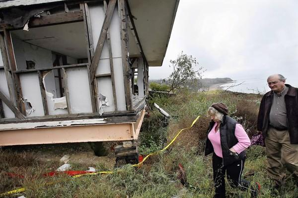Andrea Joannou and her attorney Douglas Beck visit a dilapidated house that she owns but can't renovate because Rancho Palos Verdes says a landslide has moved it onto city property