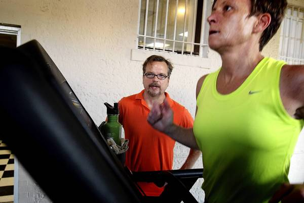 Tom Stanley the owner of Sculpt Yours Personal Training in Hampton watches as client Caroline Diehl warms up on a treadmill. Stanley does training in his Queens Way gym in Hampton but also takes clients on hiking and kayaking trips as other ways to stay physically active.