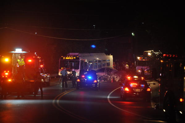 The accident scene on Eighth Avenue in Glen Burnie Saturday night, when, police said, a Lincoln LS (center rear) failed to navigate the bend in the road and collided with a No. 14 MTA bus. The car's driver, Marcus Antonio Anderson, 27, of Odenton, was killed and his young passenger was injured. The bus driver and passengers  were treated at an area hospital for minor injuries.