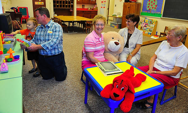 Three-year-old Colton Hahn shows Emmanuel United Methodist Church Pastor Randy Reid a movie collection while Mother's Day Out committee members Lorraine Golden, Peggy Dudley and Edith Hahn watch during a meeting to discuss the program.