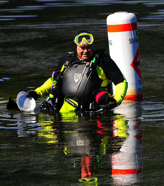Diver John McMillan of Smithsburg brings up a styrofoam plate and a foam football Sunday from Greenbrier Lake. He was diving with Blue Marble Divers to clean the swimming area at Greenbrier State Park.