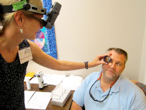 Dr. Serena A. Morrison from the West Virginia University Department of Ophthalmology gives an eye exam to William McLeod of Shepherdstown, W.Va., during a free eye clinic Friday at the Eastern Panhandle Free Clinic.