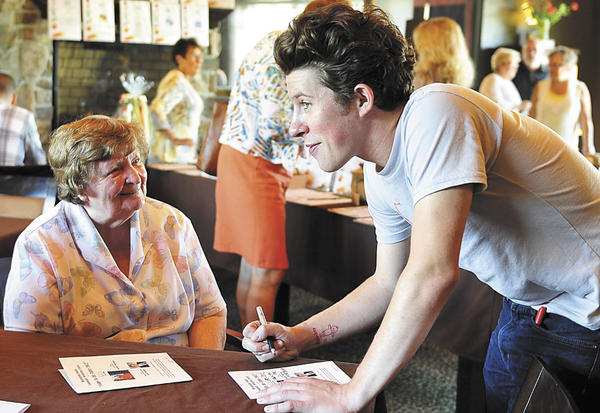 Bonnie Rice waits as Food Network personality Justin Warner, a former Hagerstown resident, considers his message before he autographs her program Sunday during a Come to the Table fundraiser at LJ's & the Kat Lounge in Hagerstown.