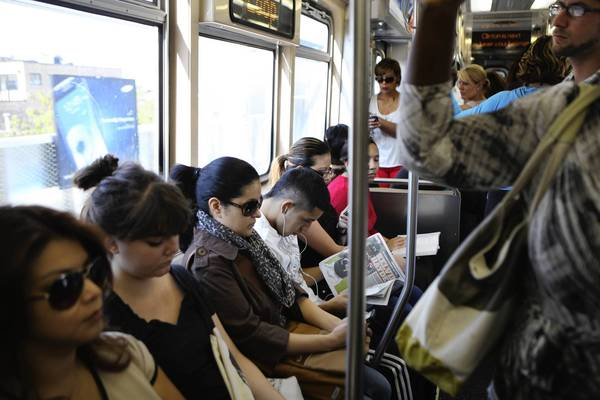Pink Line riders sit side-by-side last month aboard one of the new 5000 series rail cars. The center-facing seats have drawn complaints, but using flat benches could offer passengers more personal space.
