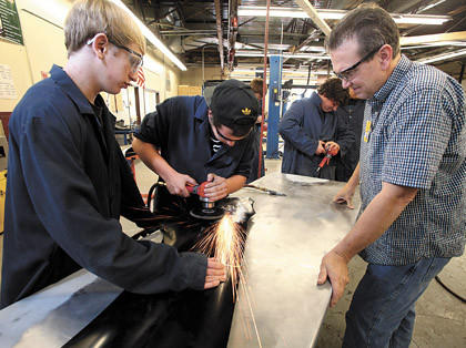 Zach Hoon, left, holds onto a fender as Steven Moinichen, center, smooths out a dent while instructor Mark Shishnia, right, looks on during the introduction to auto body class Thursday at Hub Area Technical School.