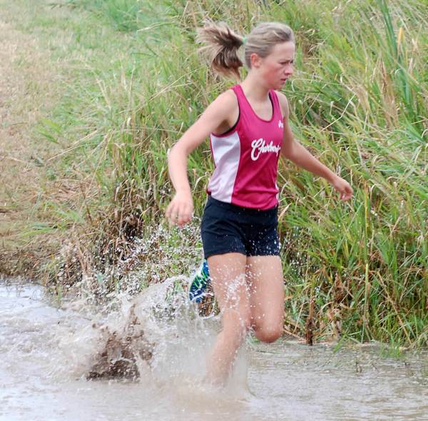 Amber Way of Charlevoix splashes through a puddle Saturday during the 21st Annual Charlevoix Classic Mud Run cross country race. Way won the 9th-10th grade girls race in 19 minutes, 44 seconds.
