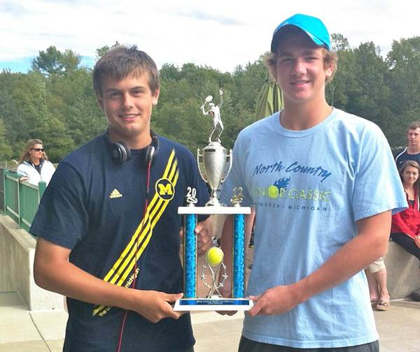 Petoskey High School tennis team co-captains Brandon Pomranke (left) and Zach Phillips display the trophy they and their teammates earned Saturday by winning the Midland High Invitational.