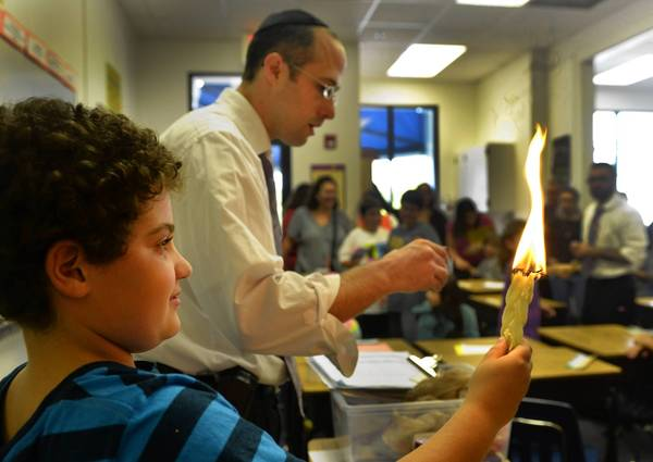 Austin Markofsky, 10 of Boca Raton holds the Haudalla candle in his Sunday School class while helping Rabbi Avi Wealcatch who gave students classes on the High Holy Days coming up next week.