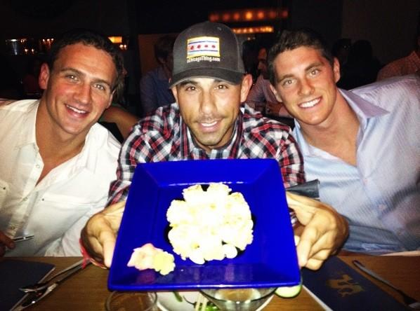 Gold medal-winning swimmers Ryan Lochte (left) and Conor Dwyer (right) at Sunda with co-owner Billy Dec (middle) and the Gold Sushi Roll August 28, 2012.