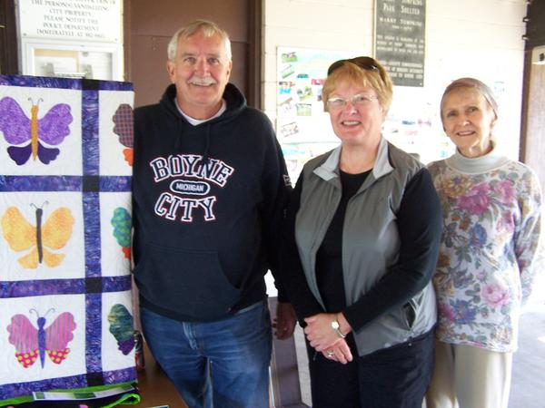 This quilt, created by The Piecemakers quilting club, was raffled at the Boyne Community Potluck Picnic to raise money for the Boyne District Library Friends of the Library. Pictured are Friends of the Library board members (left to right) Gene Ratigan, Linda Burget and Lorraine Rauen.