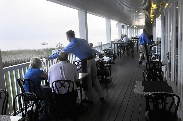The Madison Beach Hotel's Wharf Restaurant features a back porch that allows for outdoor eating along the beach.