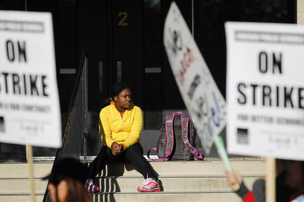 "A young girl sits on the steps of Disney Magnet School in the 4100 block of North Marine Drive in the Lakeview neighborhood of Chicago as about 150 teachers marched in front chanting, ""Rahm, Brizard, we're no fools. We won't let you ruin our schools."""