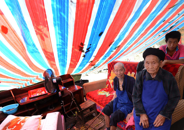 Elderly members of the Peng family sit in their makeshift shelter on September 10, 2012 after their home was badly damaged after a series of earthquakes hit Yiliang County, Yunnan Province on September 7.  Rescuers searching for survivors from twin earthquakes that struck southwestern China battled blocked roads and downed communications as the death toll rose to 80.