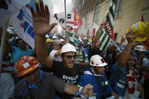 Employees of Alcoa, one of the world's leading producers of aluminum, shout slogans as they take part in a demonstration outside the industry ministry in Rome.