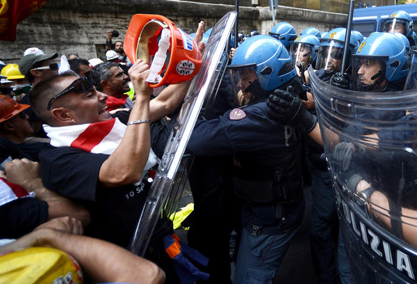Alcoa employees clash with police during the demonstration outside the industry ministry in Rome.