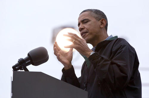A light shines behind President Obama as he speaks during a campaign event at Bayliss Park in Council Bluffs, Iowa.
