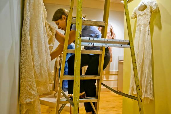Rachel Zilinski prepares a dress for an exhibit of 19 historical wedding dresses that opens this month at the Wethersfield Historical Society.