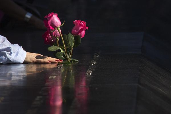 A woman lays her hands over the names of the first responders next to roses placed along the South Pool of the 9/11 Memorial at Ground Zero in New York on Sept. 10.