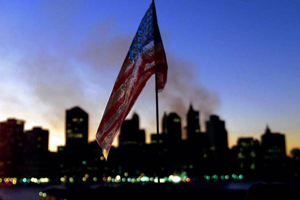 A plastic American flag sits flacid at a Brooklyn park as the sun sets in the west over a smoldering Manhattan skyline, on September 16, 2001.