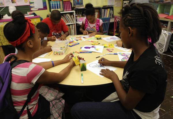 As teachers strike, hundreds of thousands of Chicago Public Schools students are missing out on time in the classroom. Among them are Divine Miner, left, and Ariell Clark, who spent part of the first day of the strike Monday coloring and playing at Crown Elementary.