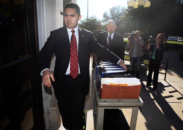 DeKalb County Assistant State's Attorney Victor Escarcida leads a group heading into the DeKalb County Courthouse on Monday before the start of the murder trial of Jack McCullough.