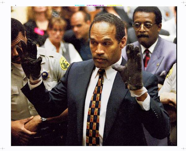 "O.J. Simpson displays the gloves to the jury. ""If it doesn't fit, you must acquit,"" defense attorney Johnnie L. Cochran Jr. told jurors"