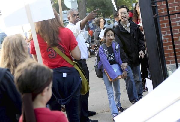 Parents and their children walk past picketing teachers outside Ray Elementary School in Chicago's Hyde Park neighborhood as they drop them off Monday.