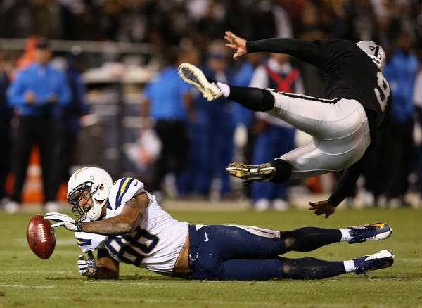 Raiders punter Shane Lechler goes flying as the Chargers' Dante Rosario goes for the ball on a blocked punt.
