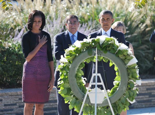 President Obama, right, First Lady Michelle Obama, left, and Defense Secretary Leon Panetta pay their respects in front of a wreath during a ceremony commemorating the 11th anniversary of the 9/11 attacks on September 11, 2012 at the Pentagon in Washington, DC.