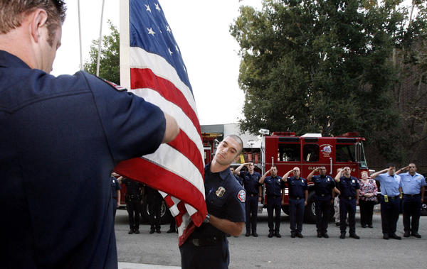 Glendale Fire Station 21 firefighters Andrew Gano, left, and Ara Hoonanian, right, raise Old Glory during 911 ceremony at Station 21 on Tuesday, Sept. 11, 2012. The ceremony, where some names of victims were read by GFD and Glendale Police, was done to commemorate those who died on Sept. 11 2001 in attacks in New York City, The Pentagon and Pennsylvania.