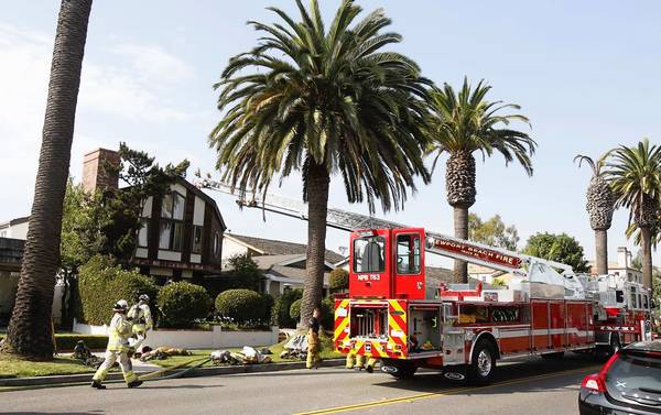 A Newport Beach fire truck extends a ladder to the roof of an apartment fire in the 600 block of Marguerite Avenue in Corona del Mar on Monday.