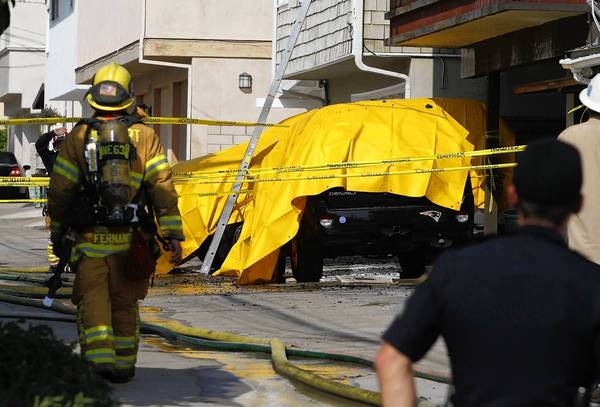 Firefighters cover an SUV with a tarp to minimize damage during the aftermath of apartment fire in the 600 block of Marguerite Avenue in Corona del Mar on Monday.