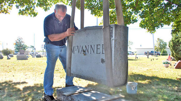 Joe Trubiro, with Patten Monument Co. of Grand Rapids, moves a headstone into place at Bagley Cemetery Monday morning. The company righted and repaired the 79 stones that were knocked over July 2.