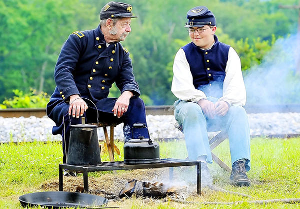 Re-enactors Larry Rita, left, of Shippensburg, Pa., portraying Union Brig. Gen. John C. Robinson, and Tyler Mullins of Manchester, Md., as a private with the 12th Massachusetts Regiment, talk while waiting for water to boil during the 2009 Mountaintop Heritage Days at Fort Ritchie in Cascade.