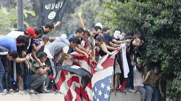 Protesters hold an American flag taken down at the U.S. Embassy in Cairo.