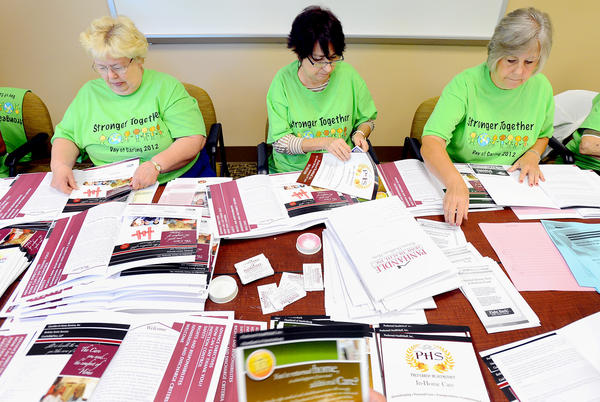 Working to fill Panhandle Home Health Inc. new patient intake information packs during Tuesday's Day of Caring are General Federation of Womens Clubs Martinsburg members, from left, Elizabeth Blackburn, Noreen Harvey and Kathy Graham.