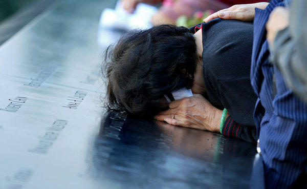 A woman cries on engravings of names on the 9/11 memorial during ceremonies for the eleventh anniversary of the terrorist attacks on lower Manhattan at the World Trade Center site September 11, 2012 in New York City.