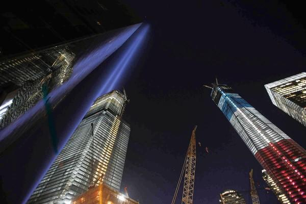 Blue lights representing those killed Sept. 11, 2001, in New York shine skyward from the ground near the site of the old World Trade Center on the 11th anniversary of the terrorist attacks. Construction of the new towers continues.