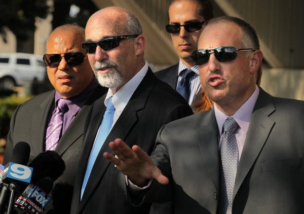 Drew Peterson defense attorneys, left to right in foreground, Joseph Lopez, Joel Brodsky and Steven Greenberg, speak to the media after the first day of testimony in the murder trial of their client at the Will County Courthouse in Joliet, Ill.