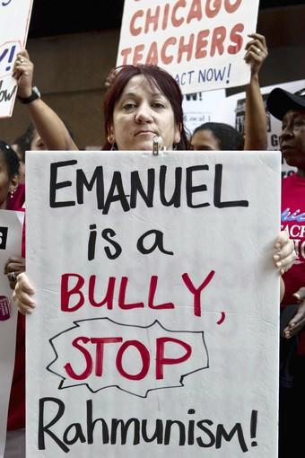 Rode Enriquez holds a sign targeting Mayor Rahm Emanuel as Chicago Public Schools teachers rally Tuesday in the Loop.