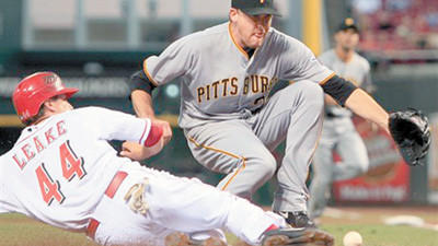 Cincinnati Reds' Mike Leake (44) scores as Pittsburgh Pirates starting pitcher Kevin Correia reaches for the ball after Correia threw a wild pitch in the second inning of a baseball game Tuesday in Cincinnati.