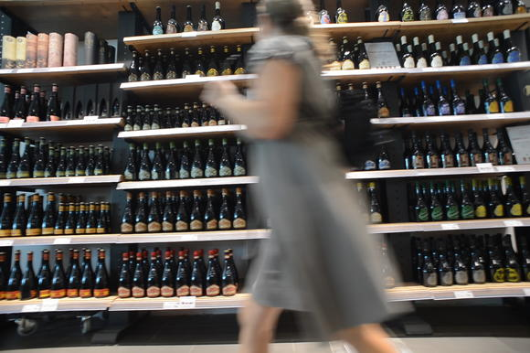 A customer walks by bottles of beer