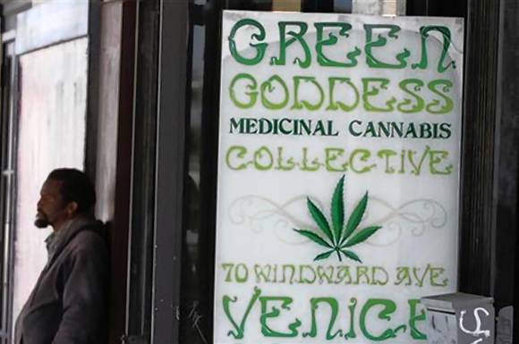 A man stands in front of a medical marijuana dispensary in Los Angeles